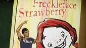 Sanjaya Malakar shows off the giant Freckleface Strawberry book cover that graces the stage at the off-Broadway production. 
