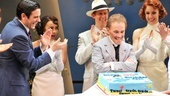 "Joel Grey admires his ""Be Like the Bluebird"" birthday cake while the Anything Goes cast looks on."