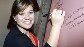 Kelly Clarkson makes her mark on the musical's backstage wall.