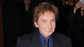 Barry Manilow signs his portrait and gives it his seal of approval.