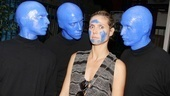 The Blue Men examine their handiwork while the shocked Project Runway host Heidi Klum tries to stay still.