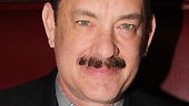 Hanks pauses for a photo while adding his autograph to the portrait, which will be forever immortalized at Sardi's.