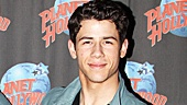 Nick Jonas poses with J. Pierrepont Finchs signature costume, a snazzy pinstriped suit and bright blue bow tie! 